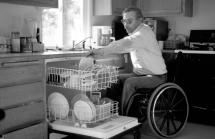 Man in wheelchair emptying dishwasher